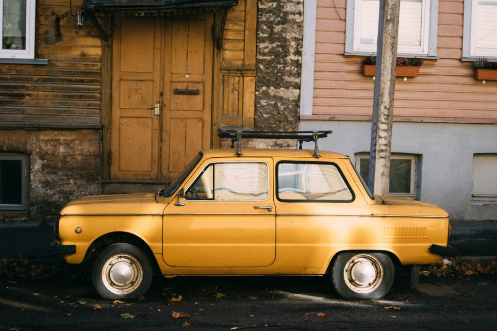 yellow retro car parked outside old building